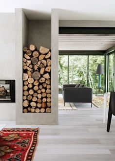 An understated fireplace encased in cement divides the living room and kitchen, while a cubby for firewood storage creates a graphic focal point. | archdigest.com