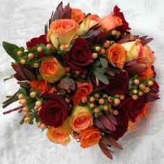 Stunning Black Magic Velvety Red Roses, Orange Unique Tangerine Roses, Ambiance Buttercup Yellow With Orangey Pink Tipped Roses Accented By Peachy Orange Hypericum Berries & Rust Safari Sunset