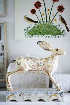 "Ceramic hare by Georgina Warne. The folk song ""Hares on the Mountains"" inspired this piece and the hare is illustrated with imagery from the verses, which Georgina has copied out across the base."