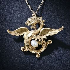 """Since antiquity the legendary griffin, with the head and wings of an eagle and the body of a lion, has symbolized courage and loyalty and is considered a great and majestic protector. In this fanciful and richly detailed gold pendant, the griffin is protecting not only the wearer, but a shimmering baroque pearl. Suspended from an 18"""" chain, this marvelous creature measures 1 inch long and 1 1/4 inches wide."""
