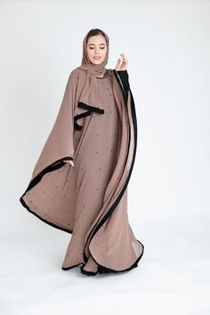 Crafted from a layer of chiffon and delicately studded with black pearls, this batwing abaya cascade into a romantic notion. Made in the UAE. Abaya Fashion, Muslim Fashion, Modest Fashion, Fashion Outfits, Women's Fashion, Mode Abaya, Mode Hijab, Modest Dresses, Modest Outfits