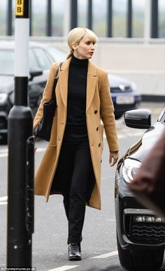Flying solo: Spotted at Terminal two of Heathrow Airport, Jennifer slipped into her character as the sexy Russian spy with ease as she sashayed across the set in a long camel trench coat