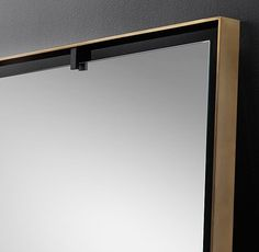 RH Modern's Niccolo Floating Mirror:Grounded in geometric simplicity, our mirror is attached to its slender metal frame with contrasting metal clips, as if suspended in space.