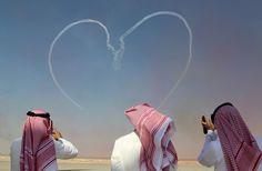 Dubai, United Arab Emirates. People take pictures as the UAE Air Force's Al Fursan aerobatics team performs during the Dubai airshow