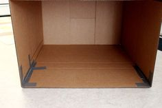 Tape up the corners of a large cardboard box.