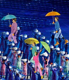 Performers with umbrellas are suspended in the air