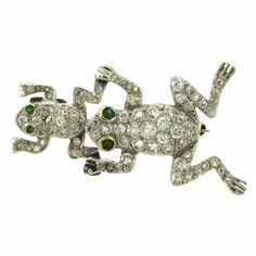 Antique Art Deco platinum frog brooch, crafted by Shreve & Co, set with emerald eyes and old mine cut diamonds. DESIGNER: Shreve & Co. MATERIAL: Platinum GEMSTONE: Diamonds DIMENSIONS: 39mm x 21mm WEI