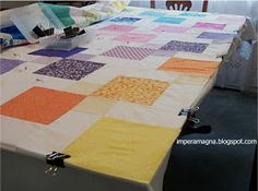 Basting a quilt w cardboard cutting mat on dining table.
