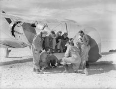 Pilots of No. 3 Squadron RAAF-Royal Australian Air Force study a map on the tailplane of one of their Gloster Gladiators at their landing ground near Sollum, Egypt, before an operation over Bardia during the closing stages of Operation Compass, January-February 1941.