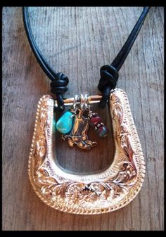 ~♥~ AN ORIGINAL DESIGN BY HEART OF A COWGIRL ~♥~ A detailed silver-tone western belt buckle is transformed into a conversation piece... a sterling silver cowboy boot charm, turquoise teardrop and czech glass beads dangle from the middle of the buckle... black leather cord completes the necklace, which closes with a sterling silver lobster claw clasp. Length is approximately 18 inches.