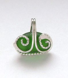 The green sea glass is genuine. It was found and supplied by.... https://www.etsy.com/shop/mamzelleseaglass. The pendant is handmade of 16 gauge round sterling wire, forged flat at the ends and 18 gauge square sterling wire that I hand twisted. It measures 1 x 7/8 inches. GN997