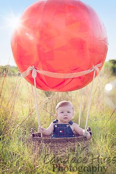"""Baby in a field, hot air balloon. DIY: basket, rods, ribbon, 42"""" beach ball with red tissue paper glued over!"""