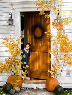 Fabulous Foliage  The best part about fall decorations is that they don't have to be complicated to look great. This no-fuss combination of orange pumpkins and golden leafed branches can create a cheery glow around any entryway.