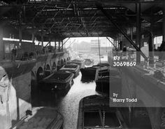 "Captioned: ""4th March 1933: An undercover unloading station for barges at Brentford Docks, situated on the River Thames opposite Kew Gardens.""  #london #barge #loading #thames #river #canal #interchange #railway #dock #brentford #transhipment #warehouse"