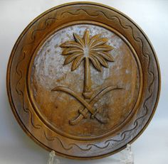 B10558 £25 inc UK Post. Offers welcome. A vintage carved wood plaque or platter with a palm tree and crossed swords at the centre, which we believe to be the emblem of Saudi Arabia. However, there is a label affixed to the underside of the plaque stating that it was made in the Philippines so presumably it was for export to Saudi. There are a few minor nibbles and rubs to the varnish but the plaque is structurally sound. The plaque measures approximately 11.75in in diameter.
