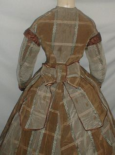 Civil War 1860's Brown Gray Silk Dress Study or Pattern | eBay A classic 1860's Civil War era brown and gray plaid silk dress. Sleeves are trimmed with pleated brown satin.  Bodice is lined with cotton and has a front button closure. Dress has an attached center back peplum belt that has a large bow and long streamers. Skirt has a back train and is fully lined with cotton. Bust 34 Waist 24 Skirt front length 38 Back length 47 Width at hemline 142.