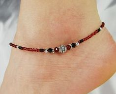 Minimalist anklet ankle bracelet made with a decorative silver pewter bead in the center, deep red crystal donuts, jet black Swarovski crystals, and red Czech glass seed beads with jet black hex seed accents. All metal beads are lead/cadmium-free Tibetan silver; clasp and other finishing-off pieces are silver-plated. SO pretty for those who love red and black together. Very wearable. Lightweight. Minimalist jewelry. Beaded anklet. Red anklet. Minimalist anklet. Spring. Summer. Beach…