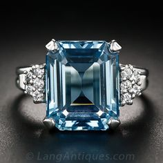 A glistening, glacier blue, emerald-cut aquamarine, measuring 6.00 carats, shines between sparkling diamond clusters in this straightforward, stunning and eminently wearable just-for-fun ring, hand fabricated in platinum sometime during the mid-twentieth century. The Aqua measures 1/2 inch by just over 3/8 inch. Stamped FFF for F. & F. Felger, New Jersey.