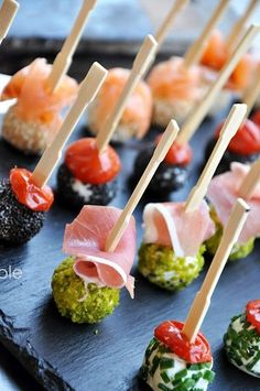 Appetizers : goat cheese rolled in sesame seeds, chives and pistachio topped with smoked salmon, tomato, and proscuitto / Billes de chèvre multicolores