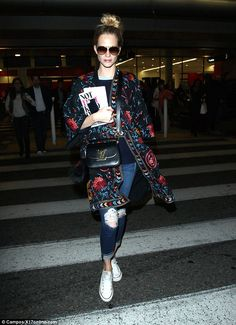 Jet-set-chic: Poppy Delevingne put her lean and frame on display as she sauntered through LAX airport while clutching onto Lena Dunham's book, Not That Kind Of Girl, on Thursday