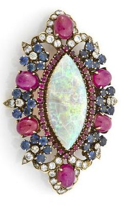 An opal, ruby, sapphire and diamond pendant/brooch navette-shaped opal measuring approximately: 35.3 x 15.4 x 3.5mm; estimated total ruby weight: 17.50 carats; estimated total sapphire weight: 5.00 carats; estimated total diamond weight: 3.25 carats; mounted in fourteen karat gold; length: 2 3/4in.