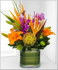 This glass cube arrives brimming with tropical flowers. The assortment includes orchids, birds of paradise and protea. The vase is lined with tropical foliage. We deliver nationwide! Tropical Flowers, Tropical Flower Arrangements, Table Flower Arrangements, Tropical Colors, Hawaiian Flowers, Exotic Flowers, Fresh Flowers, Silk Flowers, Beautiful Flowers