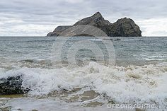 View from  the beach at the Atlantic Ocean on Porto Santo Island near Madeira Island in side of the small island (Big rock) . Portugal.
