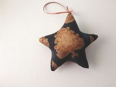 This a cute stuffed Christmas star ornament pillow made by my young niece Kate. It is made from a black fabric with brown tree shapes that are