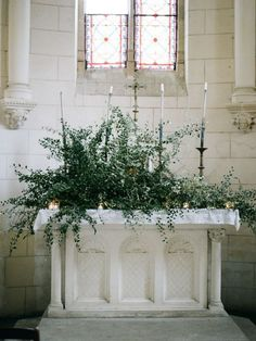 Paris, France wedding at Chateau Bouthonvilliers with blush, peach, and white wedding flowers by Foraged Floral. Large greenery installation inside French chapel for wedding ceremony. #weddingceremony #weddingflowers