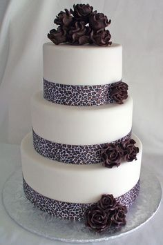 3 tier fondant cake with animal/llepoard print ribbons and brown chocolate flowers