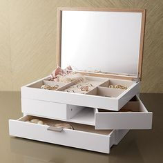 Contemporary jewelry box unfolds to a treasure chest of roomy storage trays lined in linen. Sectioned top shelf holds rings and things, two side swing drawers store bracelets and such, and an undivided lower drawer stows necklaces and other large pieces. Ash veneer lids flips open to a mirror. Linen lining and brushed silver hardware complete the look.