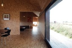 At a fraction of the size of Ochre Barn, Stealth Barn is just one clear shot down the hall from the kitchen to the bedroom. OSB is an even stronger part of the interior here evoking bales of hay. Photo by Christoffer Rudquist.