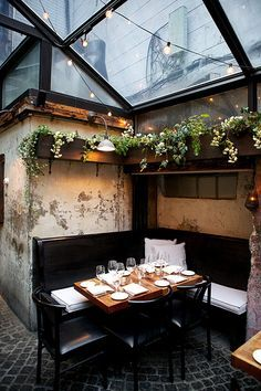 dining nook / glass ceiling / monochrome tesselated tile floor / planter boxes | August Restaurant, NYC