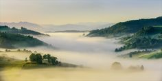 by Ioan Chiriac - Morning Light and fog over Holbav Village Hills in Brasov County, Romania