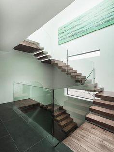 Escada com degraus em madeira de demolição e guarda corpo em vidro para dar leveza