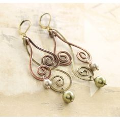 "These handmade long wavy swirls dangles made with copper and brass 16 gauge wire adorned with cream and sage green Swarovski pearls and hang on lever back antique finish earwires.    They were hammered, tumbled and oxidized in different antique tones and hand polished for more strength and character.    The earwires could be replaced with oxidized sterling silver ones at your request.    The earrings are 3""(7.5cm) in length in total.    Price: $26.00"