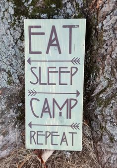 """This rustic 5.5"""" x 12"""" wooden sign with a simple statement of the perfect schedule is just the right size for a camper or cabin! EAT SLEEP CAMP REPEAT Sage green background with brown lettering and design. Custom orders are welcome! All items I have for sale are crafted by hand, rather than mass produced as you would find in a store. Because of this, your piece may slightly vary from photos shown. My wood signs are often made from reclaimed wood and pallets. They will vary slightly from…"""