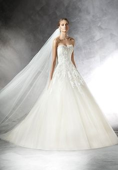 A-line wedding dress in beige tulle with appliqués Bodice with sweetheart neckline decorated with gemstones at the front and back. Wide skirt of plain tulle with appliqués. The Knot provides price estimates to give you a general idea of the cost of a dress. Please visit retailers in your area for exact pricing. Prices will vary by region.
