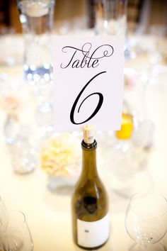 diy wine bottle table numbers for wedding reception #tablenumbers #diy #weddingchicks http://www.weddingchicks.com/2014/01/30/pink-and-peach-bejeweled-wedding/
