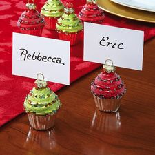 """Christmas Cupcake Place Holders. Here's a tasteful treat for everyone at the dining table! Festive glass cupcake holders come in red and green with silver liners and gold toppers. Each is 1 3/4"""" across and 2 1/2 """"H. Perfect with our set of 24 white place cards, 1 3/4 """"x 3 each, sold separately at bottom. Set of 6 (3 of each Color). Price: $12.00"""