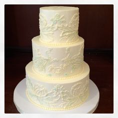 Completely piped and then hand painted with a super light touch for this elegant wedding cake. The patterns were inspired by the linen being used for the cake table and a tea towel that is super special to one of the brides. Photo by Sugar Flower Cake Shop. www.sugarflowercakeshop.com