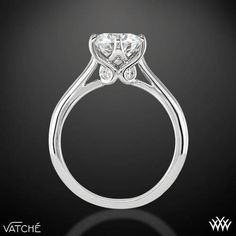 Superb craftsmanship is on full display with the Vatche 'Swan' Solitaire Engagement Ring. This 6 prong beauty incorporates an open cathedral style shank with four surprise diamonds (0.07ctw; G/VS) nestled within the gallery of the head for that extra little sparkle. This is the sister ring to our <u><b><a href='http://www.whiteflash.com/engagement-rings/three-stone/3-stone-swan-diamond-engagement-ring-by-vatche-1463.htm'>Vatche 3 Stone 'Swan' Engagement Ring</a></b></u>. The width of this…