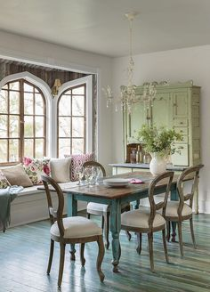 The aged-to-perfection dining table in a vivid aqua hue and the stunning sage cupboard give the dining room old-school charm.