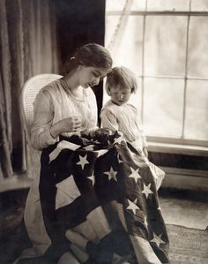 A child watches as a woman sews a star on a United States flag, 1917.
