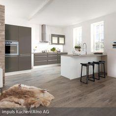 Das Schaffell auf dem Fußboden, die Wand in Mauer-Optik und die Feuerstelle setzen natürliche Akzente in der modern eingerichteten, offenen Küche. Eine  …