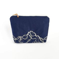 This embroidered purse in free-hand machine embroidered using white thread on Japanese navy cotton. The design resembles a marbled effect. YKK