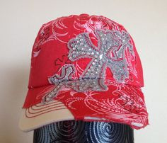 This distressed red baseball cap features a light pink screen printed pattern across the front and bill of the hat. There are small cross outlines embroidered all over the front and bill of the hat with brown thread and the front left corner of the hat is 'torn' back to reveal white fabric for a fun asymmetrical look. Also featured on the hat are three grey crosses, with a red contrast stitching outline, embellished with white rhinestones.
