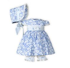Sky Blossoms and Stripes Newborn Girls Easter Dress The Wooden Soldier Exclusive Blue and white striped waistband with sweet bunny and flower appliqué. Button back closure. Tie back sash. White pull-on bloomer with eyelet trim and blue bow accent. Below knee length. Adorable sister dresses in blue cotton with white floral print. Machine wash. USA made exclusively for THE WOODEN SOLDIER.