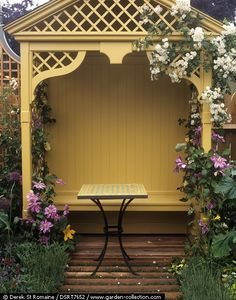 Arbour and table surrounded by clematis and roses