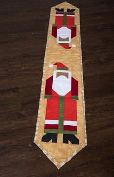 Christmas quilted table runner with black Santa on it. Primarily in gold and red tones. Really pretty!!  Measures approximately 10 x 60  Made with love in a smoke free home